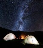 Accoppi i turisti vicino a fuoco di accampamento ed alle tende sotto cielo notturno in pieno delle stelle e della Via Lattea Immagine Stock Libera da Diritti