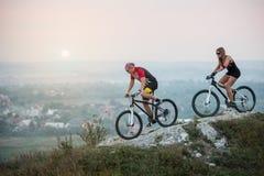 Accoppi il ciclista con i mountain bike sulla collina al tramonto fotografie stock