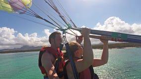 Accoppi il parasailing di parapendio del selfie vicino alla linea costiera in Mauritius stock footage