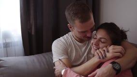 Accoppi il rilassamento insieme sul sofà Giovani coppie felici romantiche che si trovano a casa in sofà che riposa divertendosi i video d archivio