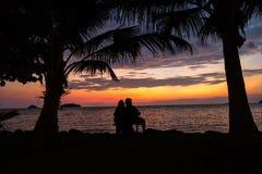 Accoppi il sole stringente a sé e di sorveglianza della siluetta al tramonto sul bea Fotografie Stock