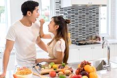 Accoppi insieme nella stanza della cucina, giovani verdure asiatiche della tenuta della donna equipaggiare fotografie stock libere da diritti