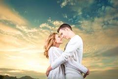 Accoppi l'abbraccio e la sorveglianza dell'uno un altro sotto il cielo soleggiato Fotografie Stock Libere da Diritti