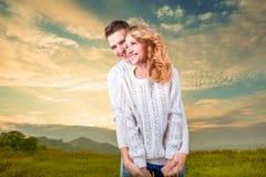 Accoppi l'abbraccio laghing e dellatenuta dell'uno un altro sotto il soleggiato Fotografia Stock Libera da Diritti