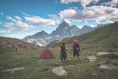 Accoppi l'esame della vista maestosa dei picchi di montagna d'ardore al tramonto alto su sulle alpi Retrovisione con la tenda di  Immagine Stock