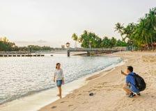 Accoppi la presa delle foto alla spiaggia di Siloso alla località di soggiorno di isola di Sentosa Immagine Stock