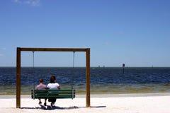 Accoppi la seduta su un'oscillazione alla spiaggia in Florida Fotografie Stock Libere da Diritti