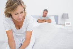 Accoppi la seduta sugli estremi opposti del letto dopo una lotta Immagini Stock Libere da Diritti