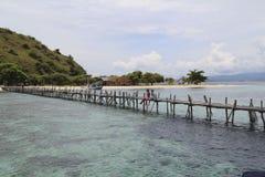 Accoppi la seduta sul ponte di legno dalla riva dell'isola Fotografie Stock