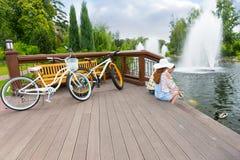Accoppi la seduta sulla piattaforma di legno dopo il ciclismo e le anatre d'alimentazione Fotografie Stock