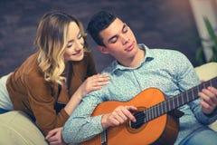 Accoppi la seduta vicino allo strato con una chitarra Fotografie Stock