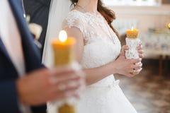 Accoppi la tenuta delle candele durante la cerimonia di nozze nel churc ortodosso Immagine Stock