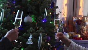 Accoppi la tostatura dei vetri con il vino bianco del champagne dall'albero di Natale illuminato decorato stock footage
