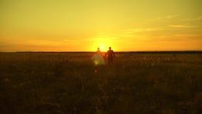 Accoppi nel tenersi per mano di amore va al tramonto L'uomo e la donna felici stanno correndo al tramonto Coppie nell'amore su un video d archivio