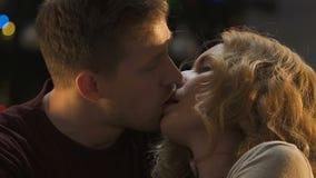 Accoppi nell'amore che bacia contro il fondo delle luci di Natale, data romantica archivi video