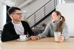 Accoppi nell'amore che si siede in caffè che si esamina reciprocamente e tenersi per mano immagini stock libere da diritti