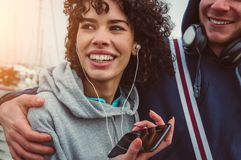 Accoppi nella musica d'ascolto di amore dalle cuffie facendo uso dello smartphone immagine stock