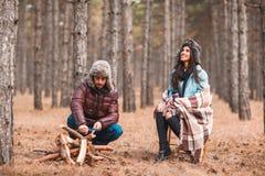 Accoppi nella ragazza della foresta A sta sedendosi ha coperto in una coperta, il tipo affila i coltelli di legno fotografie stock