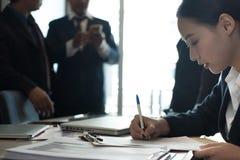 Accord contractuel d'affaires de signe de femme d'affaires la femme écrivent sur p images stock