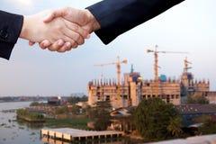 Accord de secousse de main de succès d'homme d'affaires au-dessus de construc de bâtiment Photo stock