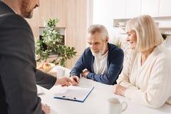 Accord de signature d'hypothèque de vieux couples bienveillants à la maison Photos stock