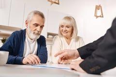 Accord de signature de couples pluss âgé résolus à la maison Image stock