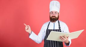 According to recipe. Man bearded chef cooking food. Culinary arts concept. Amateur cook read book recipes. Man learn. Recipe. Try something new. Cookery on my royalty free stock photo