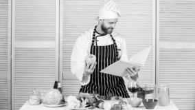 According to recipe. Man bearded chef cooking food. Guy read book recipes. Culinary arts concept. Man learn recipe royalty free stock image