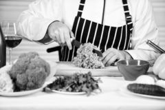 According to recipe. Useful for significant amount of cooking methods. Basic cooking processes. Man master chef or. Amateur cooking food. Sharp knife chopping royalty free stock images