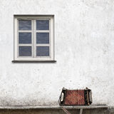 Accordion on the bench. Near the wall with a window background Stock Photos