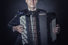 Accordion. Closeup of musician playing the accordion on a black background stock image
