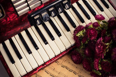 Accordion keys. Old notes and a bouquet of flowers, a nostalgic music vintage arrangement royalty free stock image
