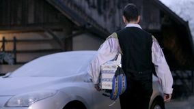 Accordion musician arrives to his car with icy windows stock footage