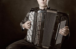 Accordion. Musician playing the accordion against a black background royalty free stock photos