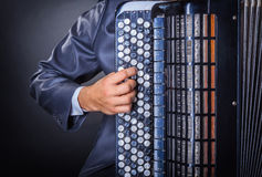 Accordion. Musician playing the accordion against a black background royalty free stock photo