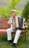 Accordion. Old man enjoying playing accordion in his garden royalty free stock image