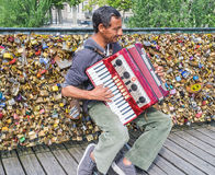 Accordion player busks in front of wall of love locks on the Pon Royalty Free Stock Photos