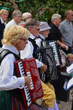 Accordion players. A group of senior Accordion players in traditional Swedish Folk costumes in a crowd of people royalty free stock image