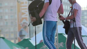 Accordion playing at a concert in sweat pants outdoors, building background stock footage