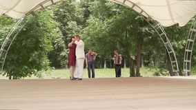 Accordion and violin playing in the park. A woman in a red dress and a man in a white suit are dancing tango. An elderly. An elderly couple dancing tango in the stock video