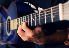Accords. The person plays a guitar, fingers hold a chord Stock Photo