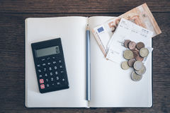 Account book concept with cash bills and coins, notebook and calculator Royalty Free Stock Image