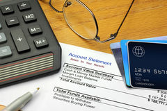 Account Statement. A financial account statement on a desk with a calculator, eye glasses, pen and generic credit card Stock Photography