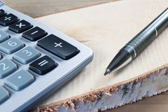 Accountancy and business concept. Calculator and pen on rustic wood. Close up royalty free stock images