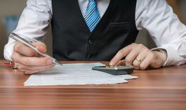Accountant or business man is calculating taxes with calculator.  stock photo