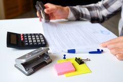 The accountant calculates. On the table business objects, calculator, stapler, hole punch, paper clips, buttons, and other office stock photo