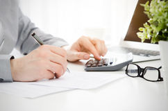 Accountant calculates tax. Working in the office with calculator Stock Image