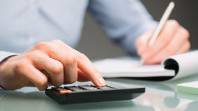 Accountant with a Calculator. A female accountant uses a calculator and takes notes on a paper notebook on an office desk stock images