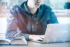 Accountant concept. Young businessman at workplace using laptop computer placed on desk with open book and abstract business diagrams. Accountant concept. Double royalty free stock image