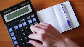 Accountant counts the balance on a calculator stock video